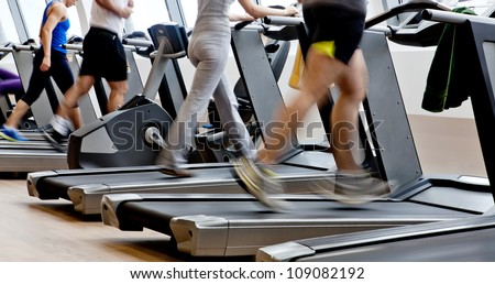 gym shot - people running on machines, treadmill - stock photo