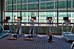gym with large windows and a stationary bike