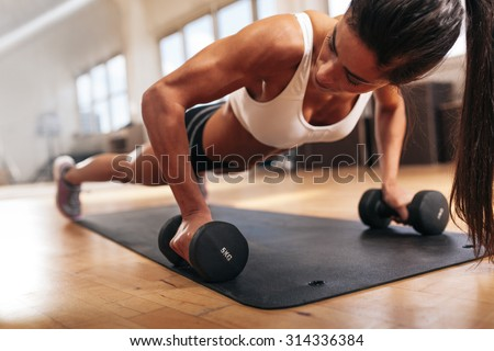 Gym woman doing push-up exercise with dumbbell. Strong female doing crossfit workout.