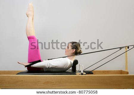 gym woman pilate instructor stretching in reformer bed