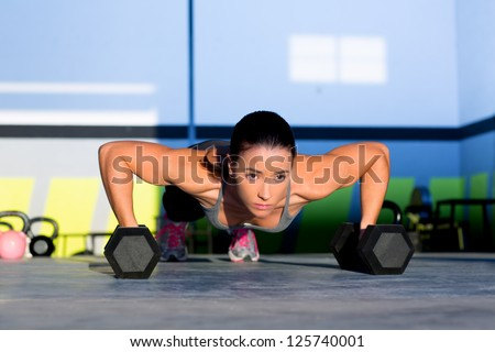 Gym woman push-up strength pushup exercise with dumbbell in a fitness workout
