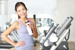 Gym woman working out drinking water smiling happy standing by moonwalker fitness machines. Beautiful fit young mixed race Caucasian / Chinese Asian female fitness model inside in fitness center.