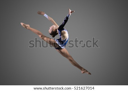 Gymnast girl doing splits in the air. Beautiful cool young fit gymnast woman in blue sportswear dress working out, performing art gymnastics element, jumping, doing split leap in the air, dancing