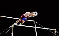 gymnastics artistic women gymnast exercise uneven bars in black background