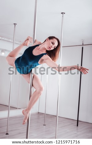 Gymnastics movements. Young but experienced pole dancer showing amazing gymnastics movements #1215971716