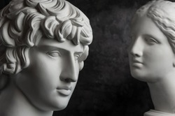 Gypsum copy of ancient statue Antinous and Venus head on dark textured background. Plaster sculpture face.
