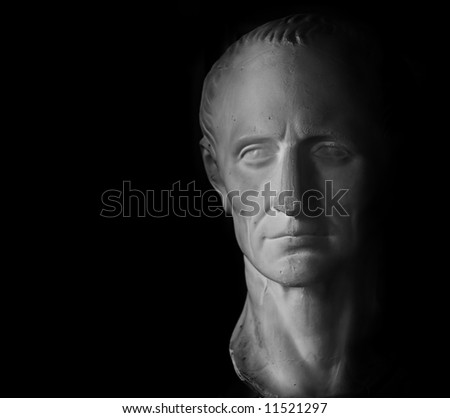 Gypsum head of Caesar on black background.