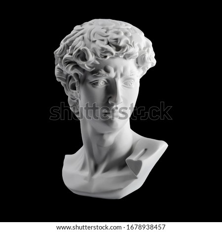 Gypsum statue of David's head. Michelangelo's David statue plaster copy isolated on black background. Ancient greek sculpture, statue of hero