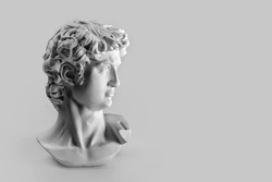 Gypsum statue of David's head. Michelangelo's David statue plaster copy on grey background with copyspace for text. Ancient greek sculpture, statue of hero