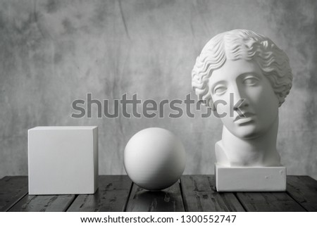 Gypsum white cube, sphere and head of an antique woman simple geometric shape on a gray fabric art background for learning to draw. Drapery and folds. stock photo