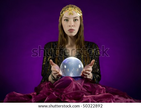 Gypsy fortune-teller,  gazes into crystalball.