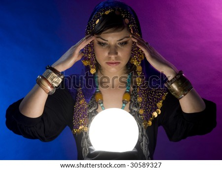Gypsy fortune-teller uses a crystal ball to foretell the future - stock photo