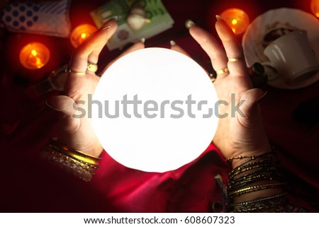 Gypsy woman fortune teller put her hands around illuminated crystal ball #608607323