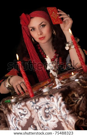 Gypsy woman sitting with cards. Isolated on black