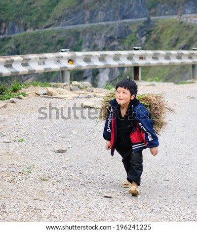 HA GIANG VIETNAM APR 29 An unidentified boy carrying grasses to home in Ha Giang Vietnam The Labor newspaper reported that 30% of Vietnamese children join the labor force On Apr 29 2014