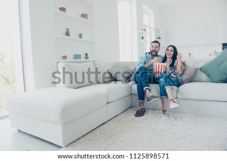 Ha-ha! Happiness joy pleasure enjoyment cinema concept. Full size portrait of positive laughters watching funny comedy eating snack sitting on sofa in modern white living room #1125898571