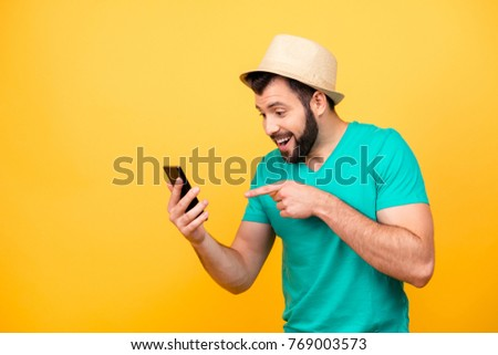 Ha-ha! So funny! Portrait of happy excited crazy man with stubble wearing hat and green tshirt, he is pointing on his smartphone and rejoicing #769003573