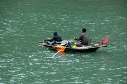 Ha Long Bay Vietnam, local men in small wooden boat fishing sustainable