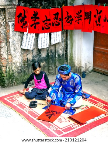HA NOI, VIET NAM, February 8, 2014 man (name unknown) was sitting writing calligraphy, had a baby girl sitting next to track and study. calligraphy of people\'s preferences Viet Nam