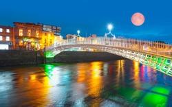 Ha'Penny Bridge at twilight blue hour with full moon - Dublin, Ireland