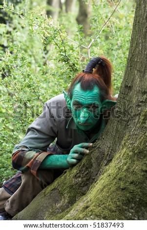 HAARZUILENS, THE NETHERLANDS - APRIL 25: Elf behind a tree at the Elf Fantasy Fair on April 25, 2010 in Haarzuilens, The Netherlands - stock photo