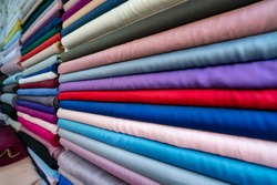 haberdasher fabric shop choice of textile material in fabric market. Shelves with colorful fabric rolls. clothes in shop, Rolls of fabric and textiles for sale stacked on shelves in shop. manifatura
