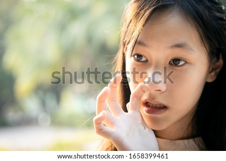 Habitual behavior of asian child girl is enjoy with finger in her nostril,hands do not wash,dirty,risk of bacterial infection into the body,woman is picking her nose due to itchy nose,nasal irritation Сток-фото ©