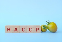 Haccp acronym in wooden blocks on blue background. Safety in food industry and manufacturing concept.