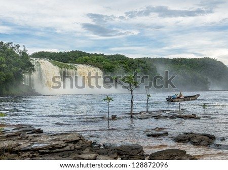 Hacha falls and tourist boat in the lagoon of Canaima national park after the storm - Venezuela, Latin America