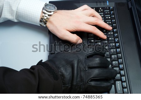 Hacker and businessman in one person working on a laptop computer, internet and identity theft - stock photo