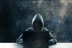 Hacker at desk using laptop with binary code. Computing and malware concept. Double exposure