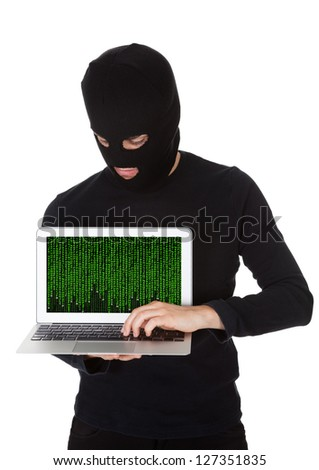 Hacker dressed in black with a mask standing stealing data from a laptop with the screen pointed towards the camera in a breach of security