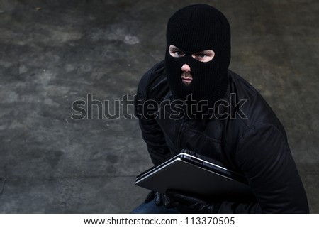 hacker holding a computer