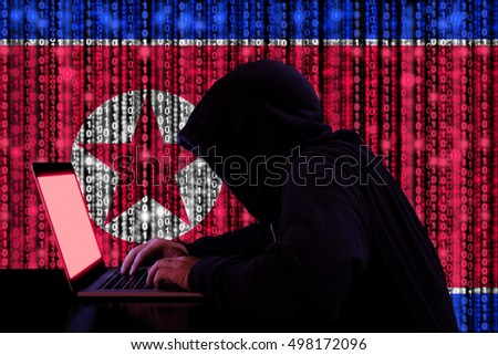 Hacker in a dark hoody sitting in front of a notebook with digital north korean flag and binary streams background cybersecurity concept