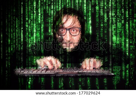 Hacker in Action on the keyboard  with matrix background