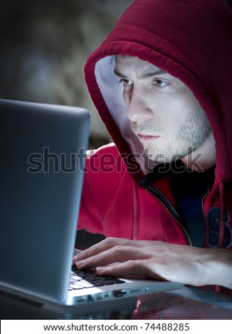 Hacker. Man with computer in a dark room