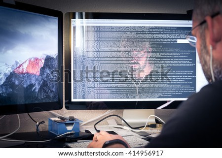 Hacker or software program developer working with computer face reflection in the monitor with code