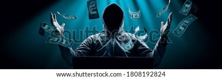 Hacker prints a code on a laptop keyboard to break into a cyberspace Stok fotoğraf ©