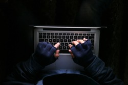 hacker stealing data from laptop, close up