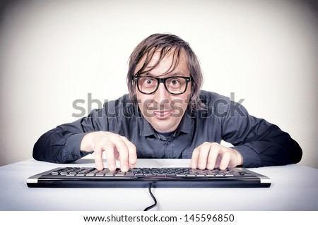 Hacker typing on the keyboard and mocking