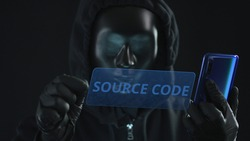 Hacker wearing black mask pulls SOURCE CODE tab from a smartphone. Hacking concept