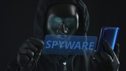 Hacker wearing black mask pulls SPYWARE tab from a smartphone. Hacking concept