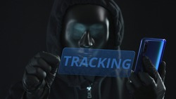 Hacker wearing black mask pulls TRACKING tab from a smartphone. Hacking concept