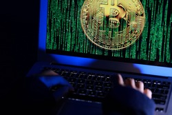 Hacker with computer hacking and stealing data information, Selective focus image on keyboard, Bitcoin logo and binary code as background. Bitcoin cryptocurrency security and privacy issues.