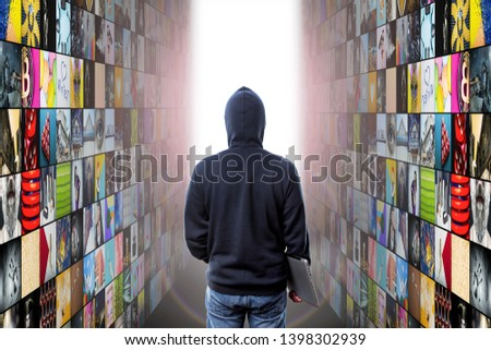 hacker with laptop enters at abstract multimedia background made from multiple colorful images #1398302939