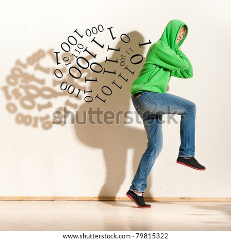 hacker. Young man is slinking along the wall with stolen computer data - stock photo