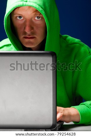 hacker. Young man with laptop is looking at camera