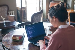 Hacking system. An excited girl with dark hair and in a pink sweater and glasses writes code on a laptop while sitting in a library. Work undercover. Girl hacker. View from the shoulder.