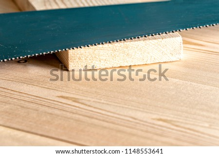 Hacksaw lies on a wooden bench