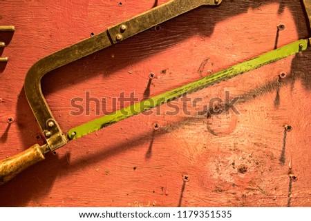 Hacksaw on metal hanging on the screws in the workshop is close
